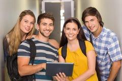 使用数字式片剂的学生在学院走廊 库存图片