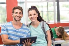 使用数字式片剂的学生在教室 库存图片