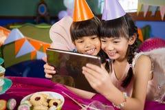 使用数字式片剂的孩子在生日聚会期间 图库摄影