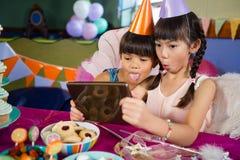 使用数字式片剂的孩子在生日聚会期间 免版税库存照片