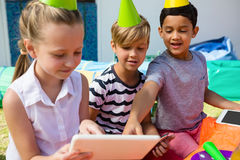 使用数字式片剂的孩子在生日聚会期间 免版税库存图片
