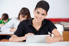 使用数字式片剂的少年男小学生画象  库存照片