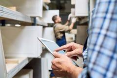使用数字式片剂的工作者在仓库 库存图片