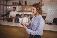 使用数字式片剂的年轻俏丽的女服务员,当待命逆时 免版税库存照片