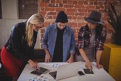 使用数字式片剂的年轻创造性的队,当站立在咖啡店时 免版税库存照片