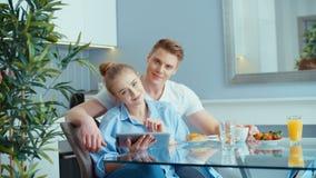 使用数字式片剂的年轻夫妇,当吃早餐在厨房用桌上时 股票录像