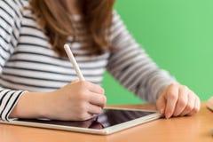 使用数字式片剂的年轻女学生文字笔记在类期间 一代Z概念 图库摄影