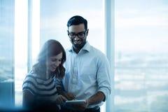 使用数字式片剂的微笑的企业夫妇反对玻璃窗 免版税库存照片