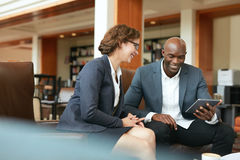 使用数字式片剂的微笑的商人在咖啡店 免版税库存图片