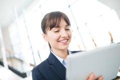 使用数字式片剂的微笑的女实业家在办公室 免版税库存照片