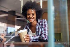 使用数字式片剂的微笑的女实业家在咖啡店 库存图片