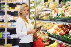 使用数字式片剂的微笑的妇女在杂货店 图库摄影