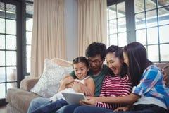 使用数字式片剂的微笑的家庭一起在客厅 免版税库存照片