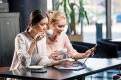 使用数字式片剂的微笑的少妇,当喝咖啡在咖啡馆时 免版税图库摄影