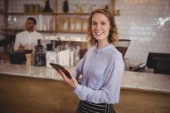 使用数字式片剂的微笑的年轻女服务员,当待命逆时 库存照片