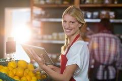使用数字式片剂的微笑的职员,当检查在有机部分时结果实 免版税库存图片