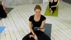 使用数字式片剂的微笑的适合的妇女画象有录影闲谈,当坐在瑜伽席子在健身锻炼以后时 股票录像