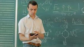 使用数字式片剂的微笑的年轻男学生反对绿色黑板 股票视频