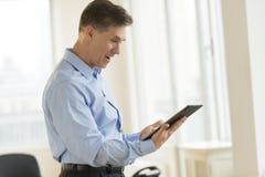 使用数字式片剂的惊奇的商人在办公室 免版税图库摄影