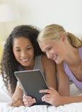 使用数字式片剂的愉快的女性朋友在床 库存照片