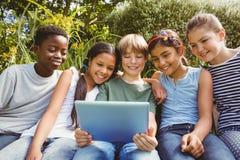 使用数字式片剂的愉快的孩子在公园 库存照片