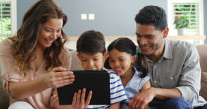使用数字式片剂的愉快的家庭在客厅 股票视频