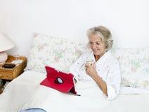 使用数字式片剂的愉快的资深妇女,当食用在床上的咖啡在家时 免版税库存图片