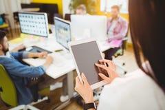 使用数字式片剂的执行委员背面图在创造性的办公室 免版税库存图片