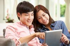使用数字式片剂的新中国夫妇 免版税库存照片