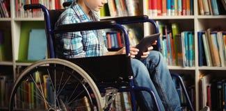 使用数字式片剂的残疾男小学生在图书馆 库存图片