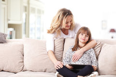 使用数字式片剂的母亲和女儿 免版税库存照片