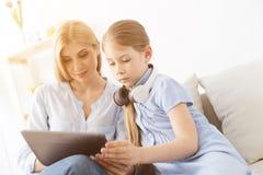 使用数字式片剂的母亲和女儿 库存照片