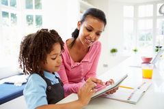 使用数字式片剂的母亲和孩子为家庭作业 图库摄影