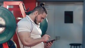 使用数字式片剂的爱好健美者跟踪他的在健身房的锻炼进展 图库摄影