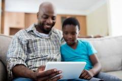 使用数字式片剂的父亲和儿子在客厅 免版税库存图片