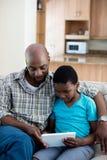 使用数字式片剂的父亲和儿子在客厅 免版税库存照片