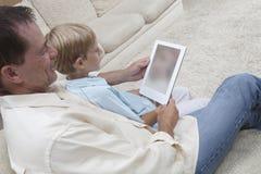 使用数字式片剂的父亲和儿子 免版税库存图片