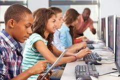 使用数字式片剂的男孩在计算机类 免版税库存照片