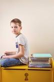 使用数字式片剂的男孩坐在bis堆书附近 库存图片