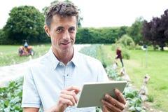 使用数字式片剂的男性农业工作者在领域 免版税库存图片
