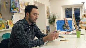 使用数字式片剂的男性画家在艺术车间 免版税库存照片