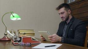 使用数字式片剂的男性研究员坐在他的有书和打字机的研究书桌 股票视频
