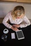 使用数字式片剂的确信的女实业家,当喝咖啡在咖啡馆时 免版税库存照片