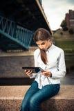使用数字式片剂的美丽的女孩 免版税库存图片