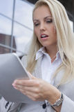 使用数字式片剂的美丽的女实业家户外 免版税图库摄影