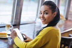 使用数字式片剂的美丽的混合的族种十几岁的女孩 免版税库存照片