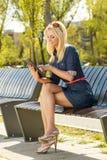 使用数字式片剂的美丽的金发碧眼的女人 免版税库存图片