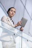 使用数字式片剂的美丽的年轻女实业家在办公室栏杆 库存照片