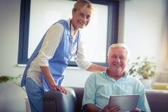 使用数字式片剂的老人和女性医生画象  免版税库存图片