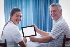 使用数字式片剂的老人和女性医生画象  免版税图库摄影